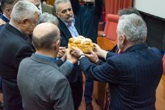 Домаћин славе и чланови управе Друштва окрећу славски колач